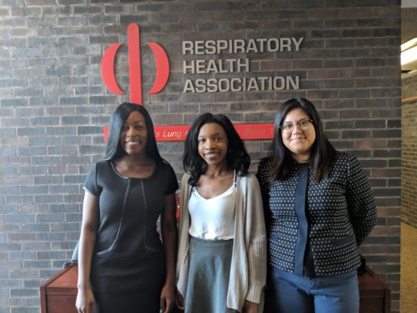 three women stand in front of a brick wall with the Respiratory Health Association logo