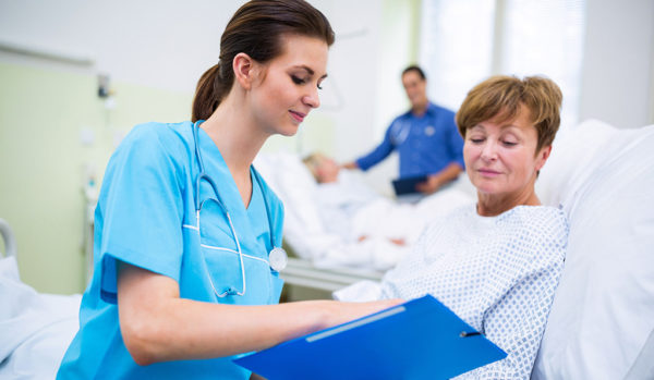 Nurse showing clipboard to patient in hospital ward