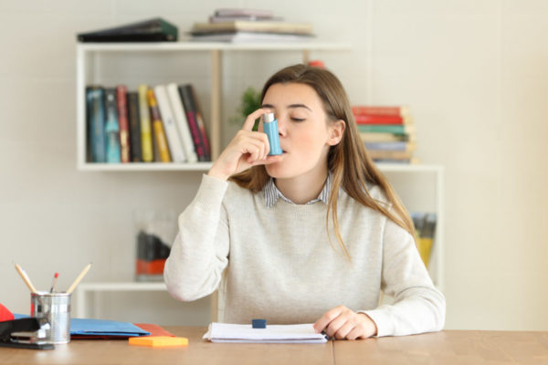 Young woman uses inhaler while in school