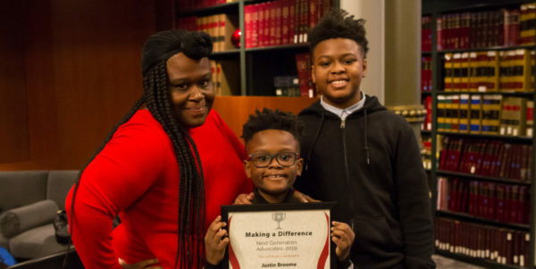 smiling family with award