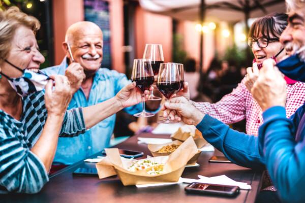 senior people toasting wine glasses summer covid-19 updates